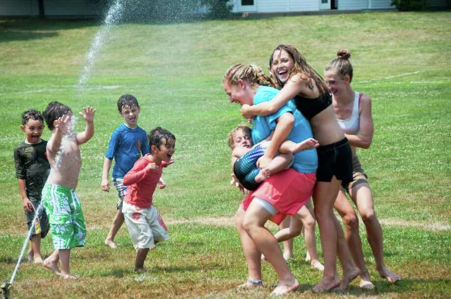 From left, Griffin Smuckler, Jonah Weinstock, Zach Smuckler, Ben Bazarian, Luke Rucolas, Aubrey Nolan, Julie Sauro and Kate McNutt have fun running through the sprinkler at Summer at Wooster Camp. The camp is held annually at Wooster School in Danbury. This photo was taken on Wednesday, July 20, 2011. Photo: Patricia Keeler / The News-Times