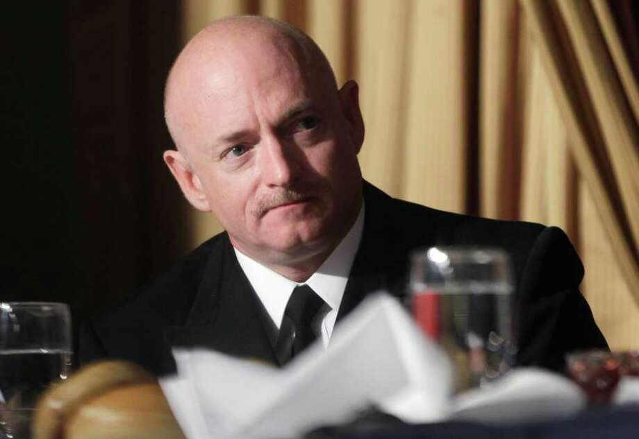 Astronaut Mark Kelly, husband of wounded Rep. Gabrielle Giffords, D-Ariz., is acknowledged by President Barack Obama, at the National Prayer Breakfast in Washington, Thursday, Feb. 3, 2011. (AP Photo/Charles Dharapak) Photo: Charles Dharapak, STF / AP