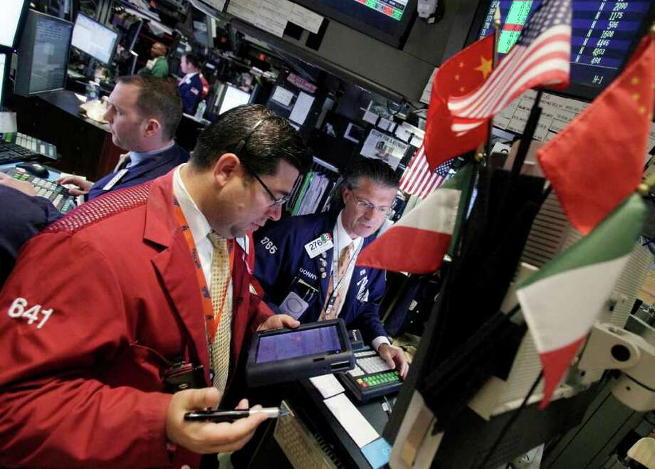 In this July 18, 2011 photo, specialist Donald Civitanova, right, directs trades at his post on the floor of the New York Stock Exchange. Global stocks rallied further Wednesday, July 20, as a raft of positive U.S. earnings reports and signs of progress over raising the U.S. debt ceiling helped offset debt concerns afflicting Europe. (AP Photo/Richard Drew) Photo: Richard Drew