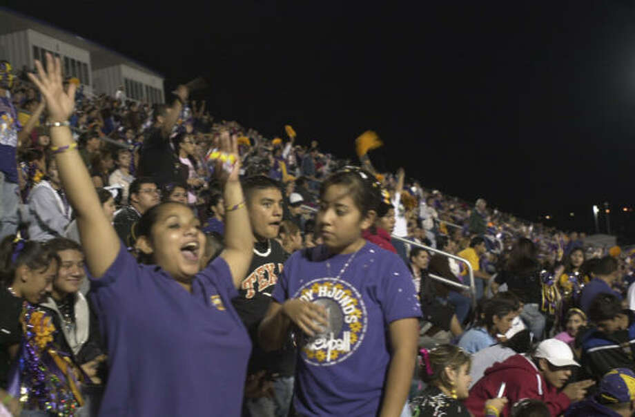 Fans cheer in the stands during a San Benito Greyhound varsity football last week. San Benito's humble reality melts away in the glare, hype and community celebration of high school football. Photo: Jesse Bogan, SAN ANTONIO EXPRESS-NEWS