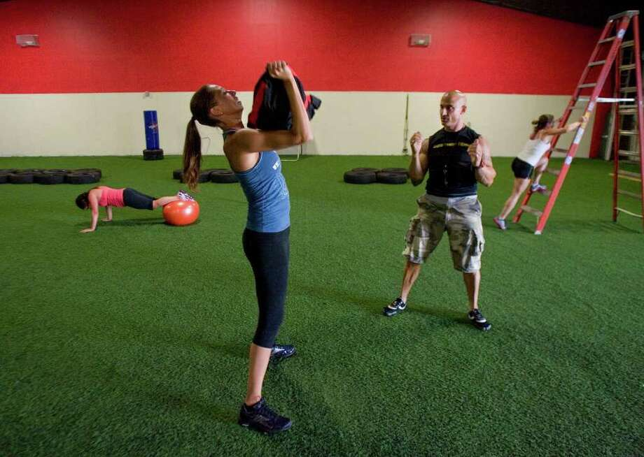 Alfonso Moretti, right foreground, gives instructions to Cat Symes, of Brookfield, as Ana Maria Rio, of Danbury, left, and Cilia Frascone, of Danbury, right, finish at their stations before moving on to another during Anger Management - The Ultimate Fitness Experience in Danbury on Wednesday, July 20, 2011. Photo: Jason Rearick