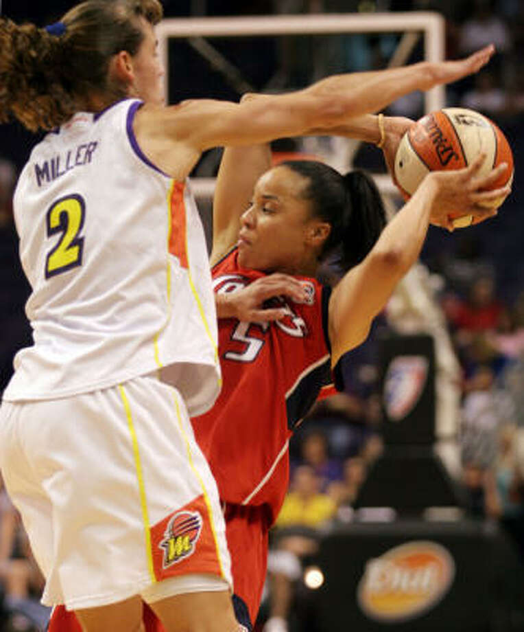 Comets guard Dawn Staley is defended by Phoenix Mercury's Kelly Miller during the first quarter on Sunday. The Comets won 82-80. Photo: ROY DABNER, AP