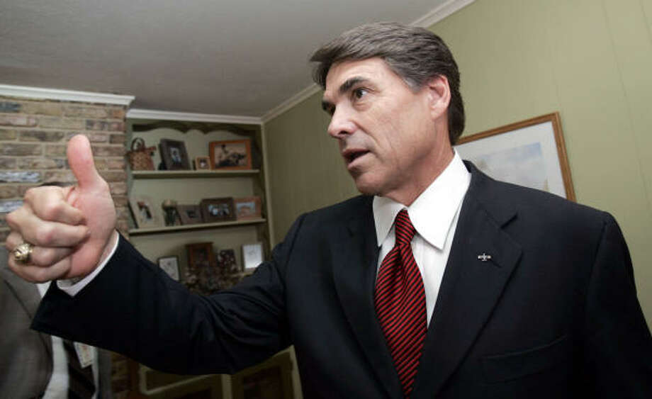 Gov. Rick Perry gives a thumbs up after a news conference at a Dallas home on Monday. State leaders looking toward the next budget face a tight money situation driven by the need to fund the new school finance package, including a cut in property tax rates. Photo: LM OTERO, AP