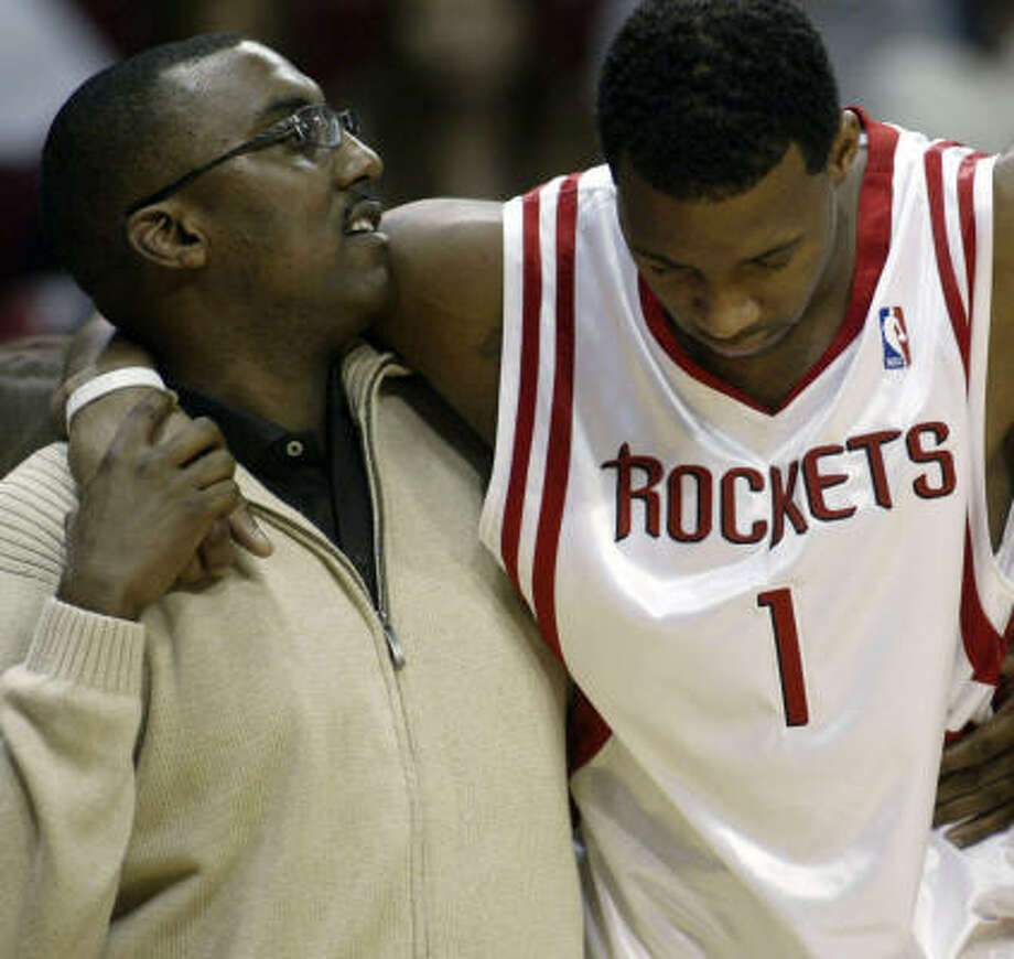 Tracy McGrady is helped off the court by trainer Keith Jones after a mild concussion. Photo: Jessica Kourkounis, For The Chronicle
