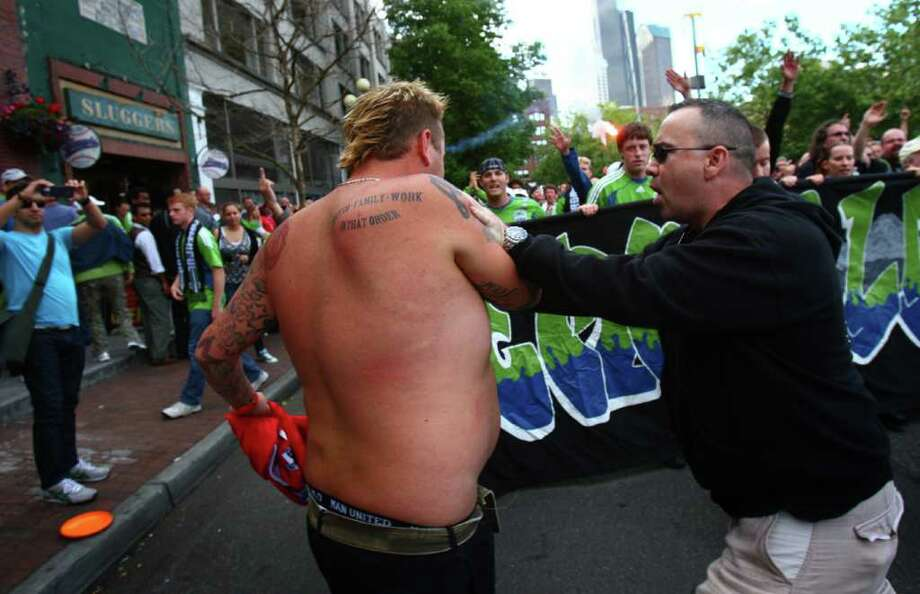 A Manchester United fan, left, is shoved out of the way by a Sounders fan during the march to the match. Photo: JOSHUA TRUJILLO / SEATTLEPI.COM
