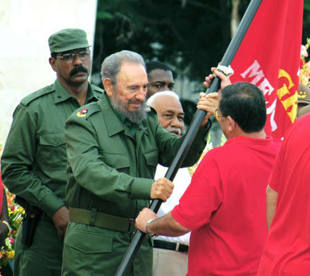 Fidel Castro presents a flag to the top Communist Party of Cuba official in Granma province.
