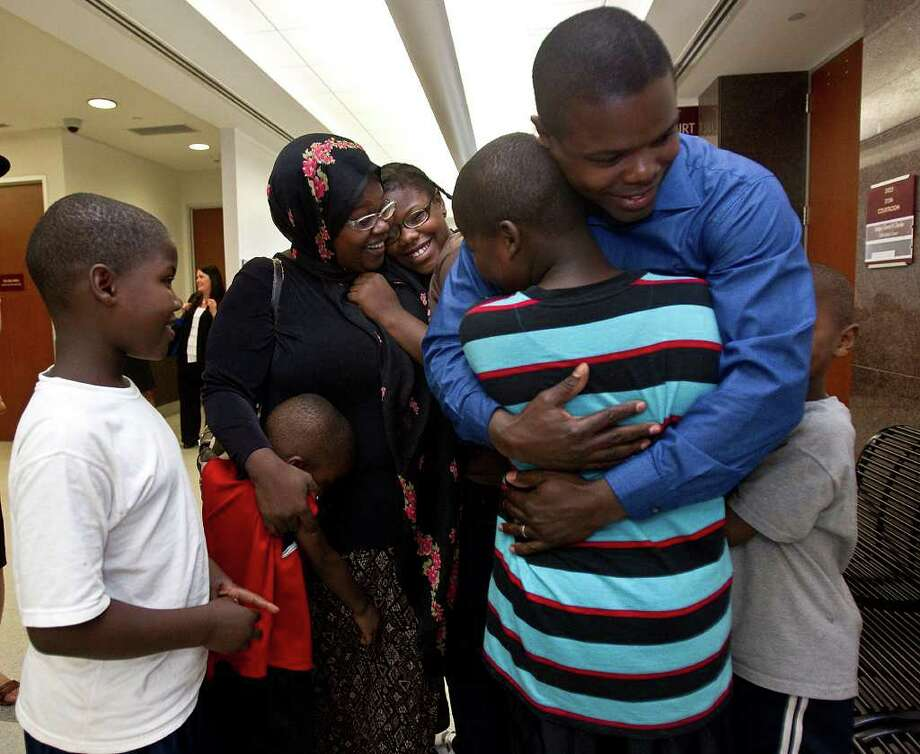 The Leonard family reunites for the first time in the hallways of the Juvenile Justice Harris County courthouse, Wednesday, July 20, 2011 in Houston, Texas.  (l-r) Eight year-old Raheem Leonard, stands by with a smile as four year-old Abdullah Leonard  hugs his mother Charlomane Leonard along with sister twelve year-old Sabrina Leonard, while ten year-old Prince Leonard II receives a hug from his father Prince Leonard, as  seven year-old Saleem Leonard stands by. A Harris County juvenile judge ruled Wednesday July 20, 2011 that a Houston couple, whose six children were removed from their custody after caseworkers found the family living in a storage shed, will be able to have their children back. (Billy Smith II / Houston Chronicle) Photo: Billy Smith II / 2011 Chronicle