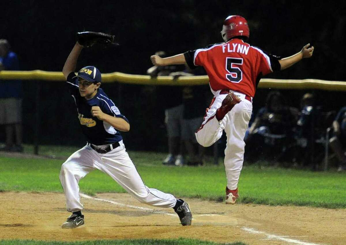Fairfield American's Brendan Flynn is safe at first as East Haven's Mike Torniero catches the ball during Wednesday's Little League sectional game in Orange on July 20, 2011.
