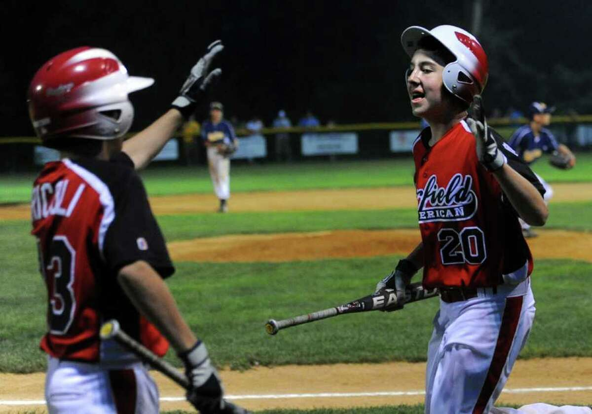 Fairfield American's Grant Carnemark gets a high-five during Wednesday's Little League sectional game in Orange on July 20, 2011.