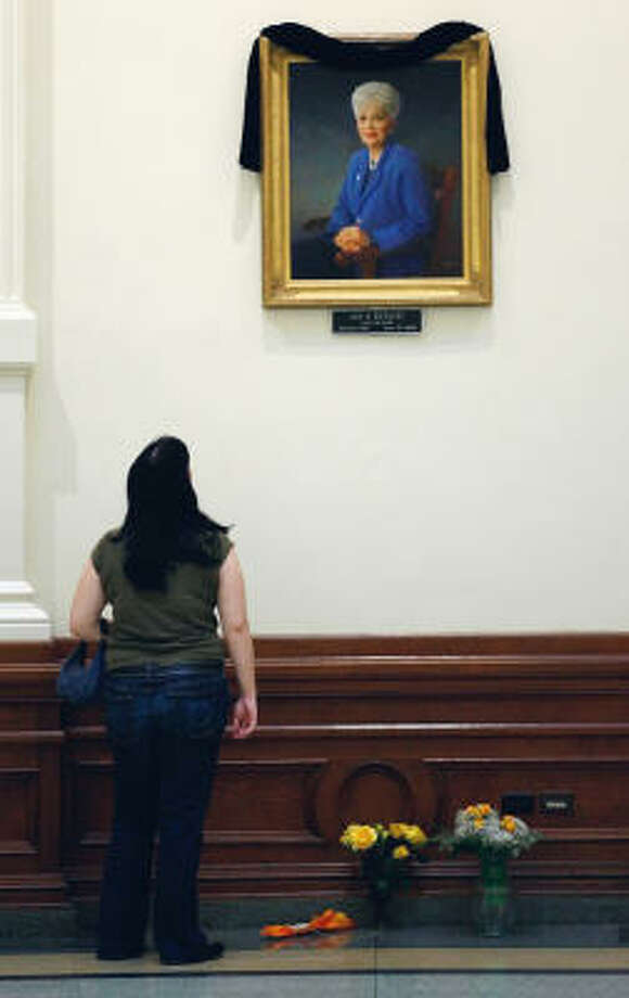 Terra Wright pays her respects after placing a yellow rose under a portrait of former Gov. Ann Richards in the Capitol Rotunda in Austin. Photo: HARRY CABLUCK, AP