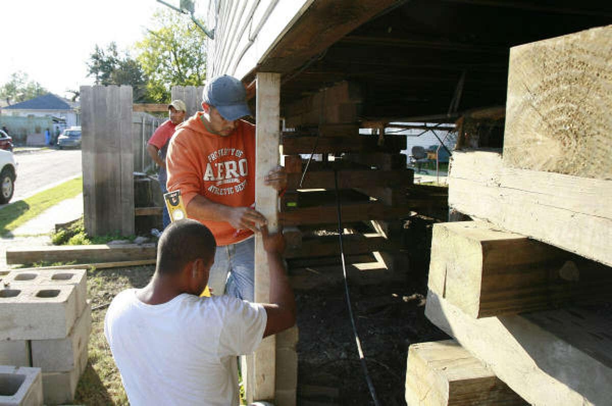 Jose Perez, top, of San Luis Potosi, Mexico, and Manual Ramirez of Zacatecas, Mexico, work on raising a house in New Orleans this month.