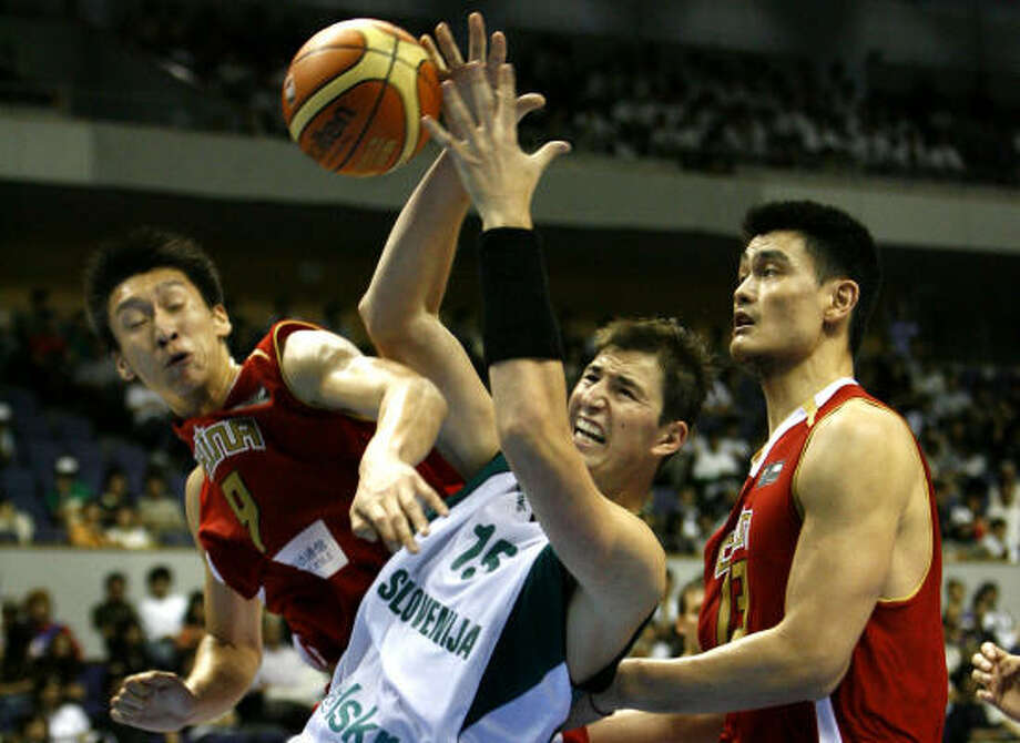 Slovenia's Primoz Brezec, center, battles for a ball under the basket with China's Yao Ming, right, and Sun Yue. Photo: DAVID GUTTENFELDER, AP