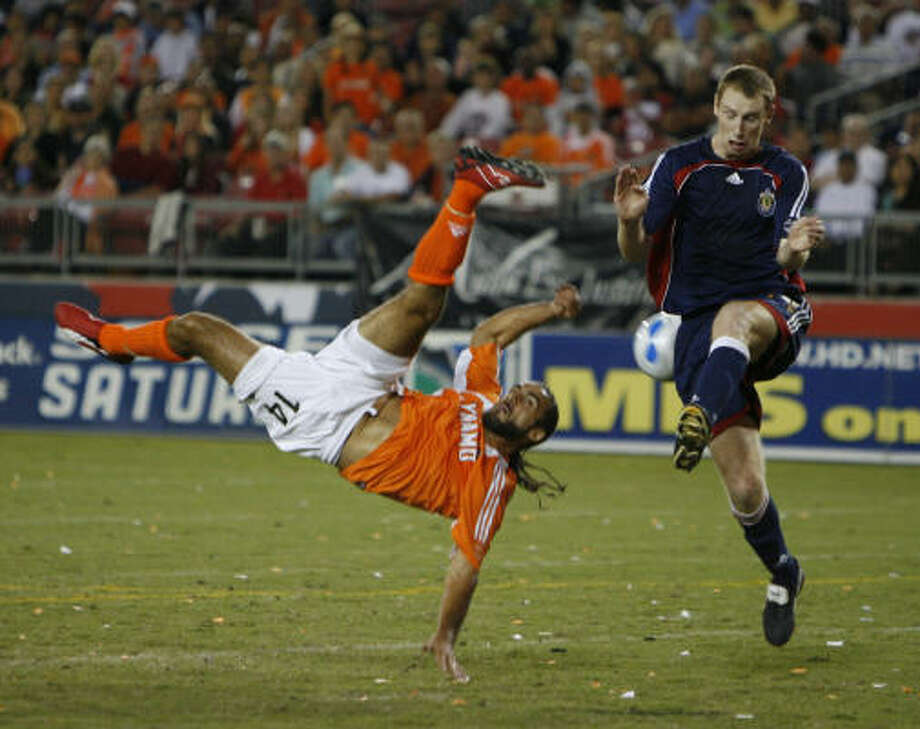 Dynamo's Dwayne De Rosario flips as he takes a shot on goal against Chivas USA. Photo: KAREN WARREN, Chronicle