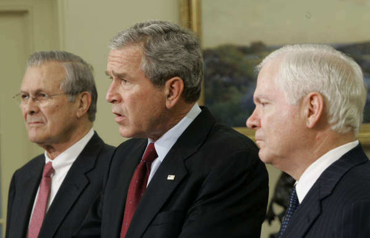 President Bush, center, flanked by outgoing Defense Secretary Donald H. Rumsfeld, left, and his Defense Secretary-nominee Robert Gates, speaks in the Oval Office today.