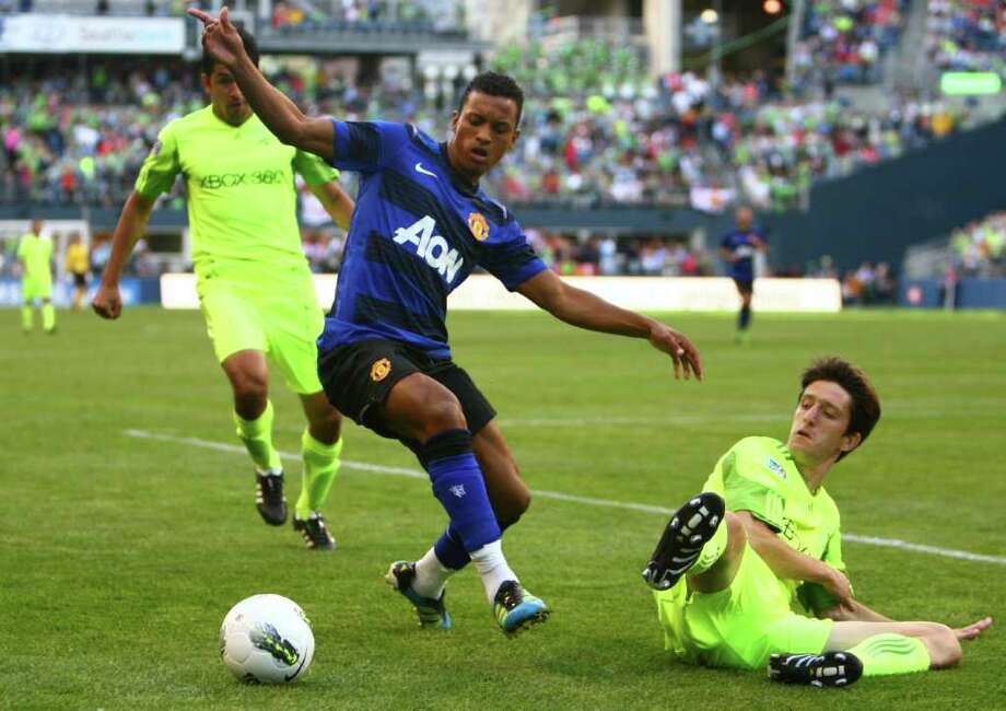 Sounders player Alvaro Fernandez, right, falls to the ground against Manchester United player Nani. Photo: JOSHUA TRUJILLO / SEATTLEPI.COM