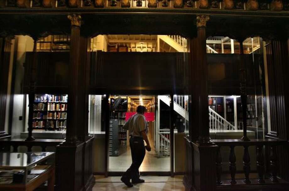 Security guard Larry Guillory walks through and checks the Houston public library's Julia Ideson building. The library is said to be haunted by a violin-playing ghost. Photo: Carlos Antonio Rios, Chronicle