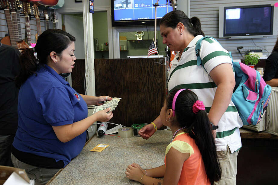 """Crystal Casias (left) helps out customer, Gabriela Rodriguez and her daughter, Stephanie Mendoza, at Bill's Pawn Shop on South Zarzamora on July 18, 2011. Rodriguez was paying off a loan on a gold crucifix. Taking possession of her crucifix, she said, """"It was given to me by an aunt."""" Photo: JERRY LARA / SAN ANTONIO EXPRESS-NEWS"""