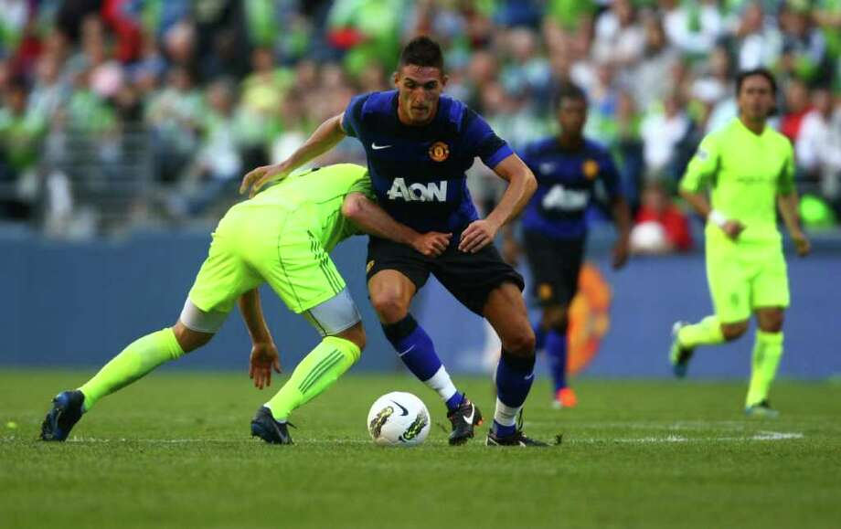 Manchester United player Federico Macheda battles with a Sounders player. Photo: JOSHUA TRUJILLO / SEATTLEPI.COM