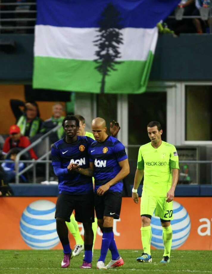 Manchester United player Gabriel Obertan, center, is congratulated by teammate Mame Biram Diouf after scoring a goal. At left is Sounders player Zach Scott. Photo: JOSHUA TRUJILLO / SEATTLEPI.COM