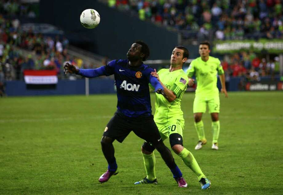 Sounders player Zach Scott defends Manchester United player Mame Biram Diouf. Photo: JOSHUA TRUJILLO / SEATTLEPI.COM