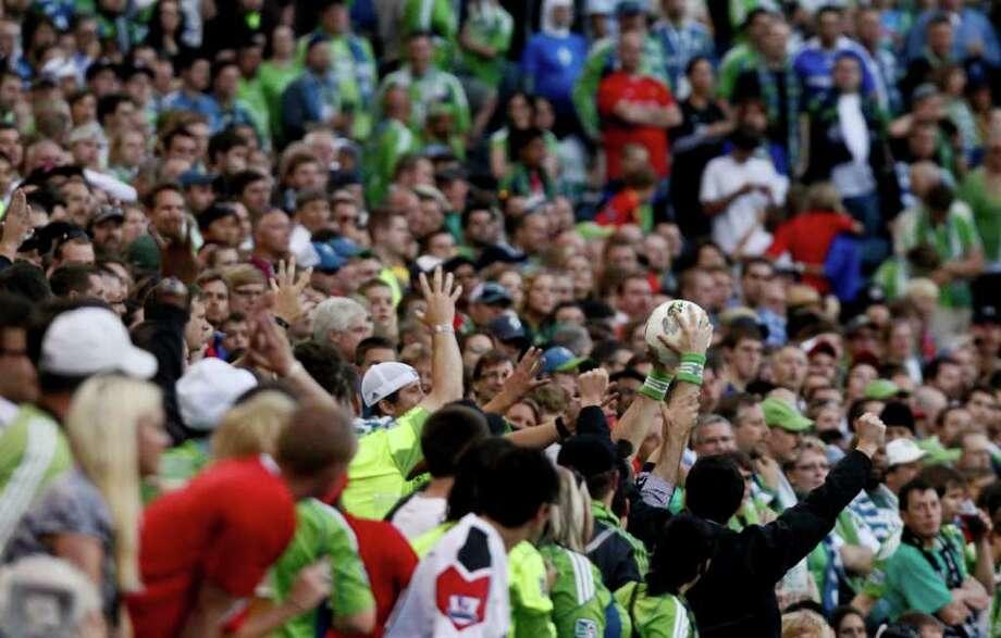 Spectators catching an out of bounds ball. Photo: JOE DYER / SEATTLEPI.COM
