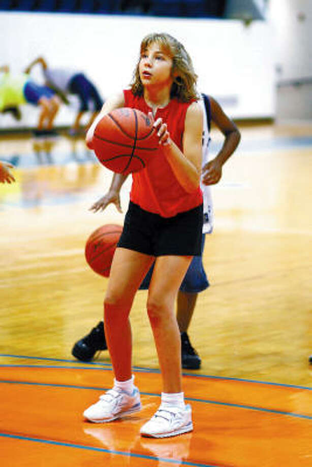 Kelli Nerren takes aim at the goal during a basketball camp in Lufkin. The 10-year-old, who has grown up without a right arm, hasn't let the disability stop her from enjoying the game she loves. Photo: GARY STALLARD, The Lufkin Daily News