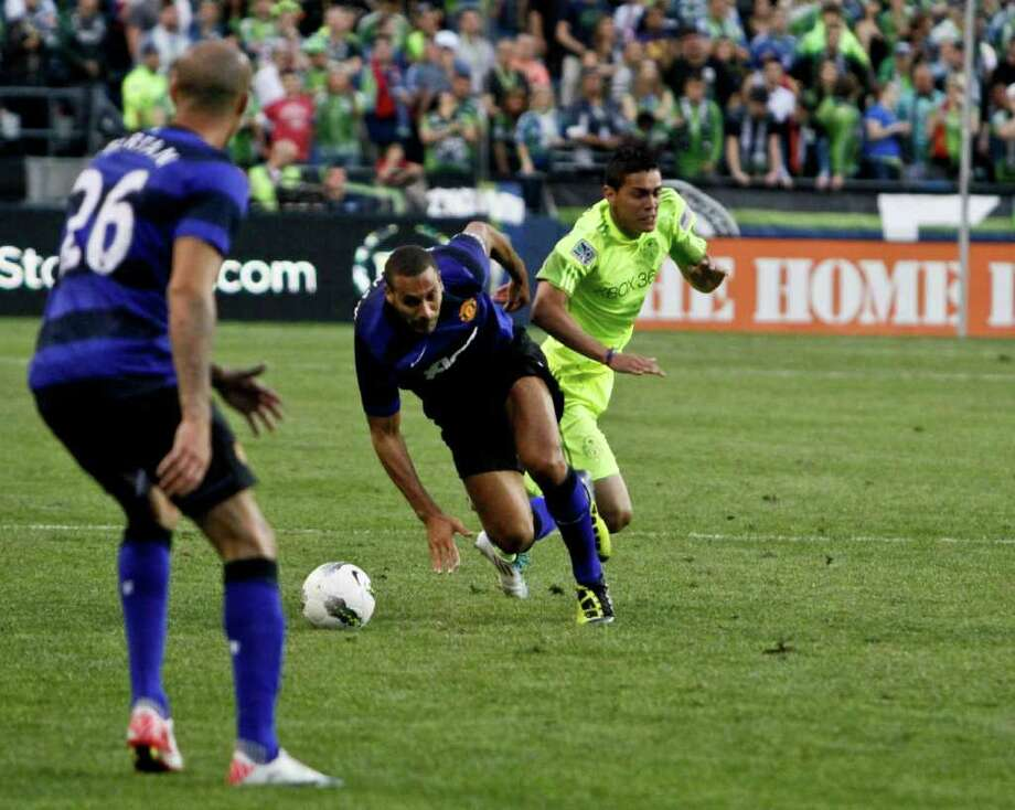 Left to right, Rio Ferdinand and Miguel Montano collide. Photo: JOE DYER / SEATTLEPI.COM