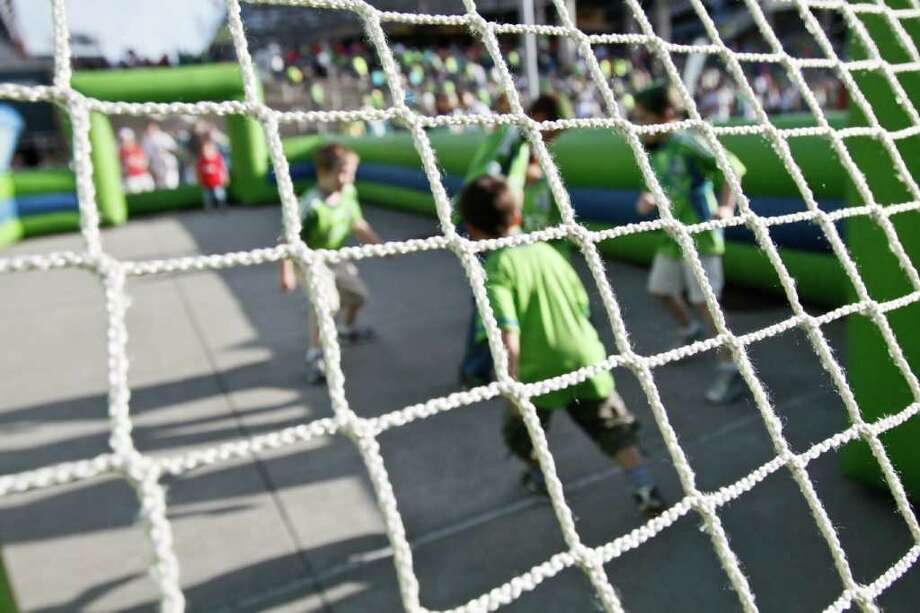 Children play in a mini inflatable soccer arena. Photo: JOE DYER / SEATTLEPI.COM