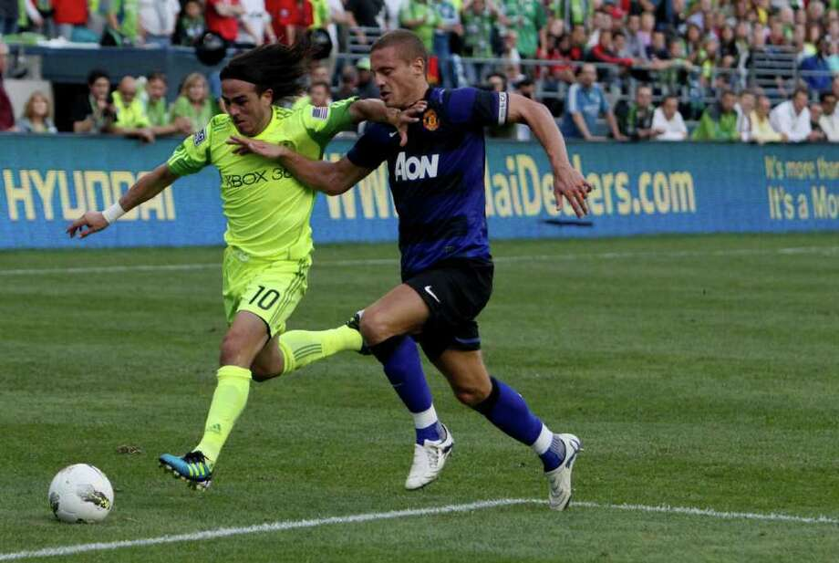 Nemanja Vidic attempts to steal the ball from Sounders player Mauro Rosales. Photo: JOE DYER / SEATTLEPI.COM