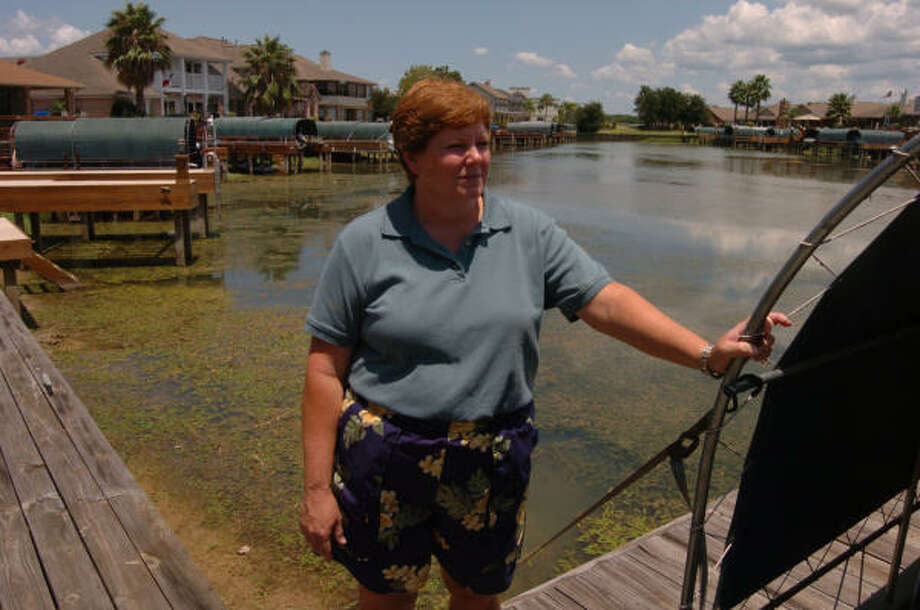 Suzanne Calhoun stands on the boat dock at her home in Pelican Bay on Lake Conroe. The water around her waterfront neighborhood was clear several months ago, and is now clogged with hydrilla. Photo: David Hopper, For The Chronicle