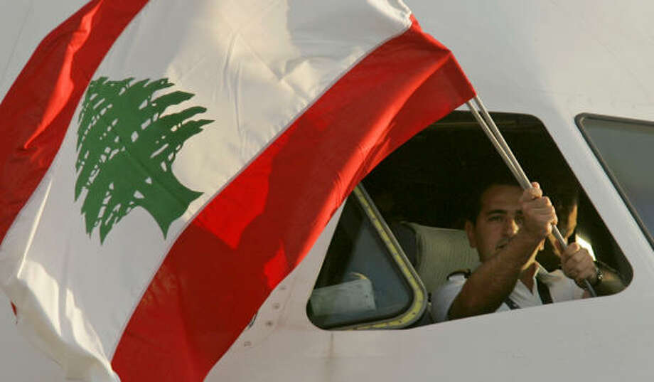 A pilot for Lebanon's Middle East Airlines waves a Lebanese flag as he lands at Beirut's airport Thursday. The direct flight from Paris was the first to land after Israel's blockade was lifted. Photo: MATT DUNHAM, AP