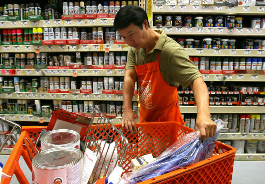 Home Depot worker Mike Nguyen restocks paint products. It's already illegal to sell spray paint to minors. Photo: Sharon Steinmann, Chronicle