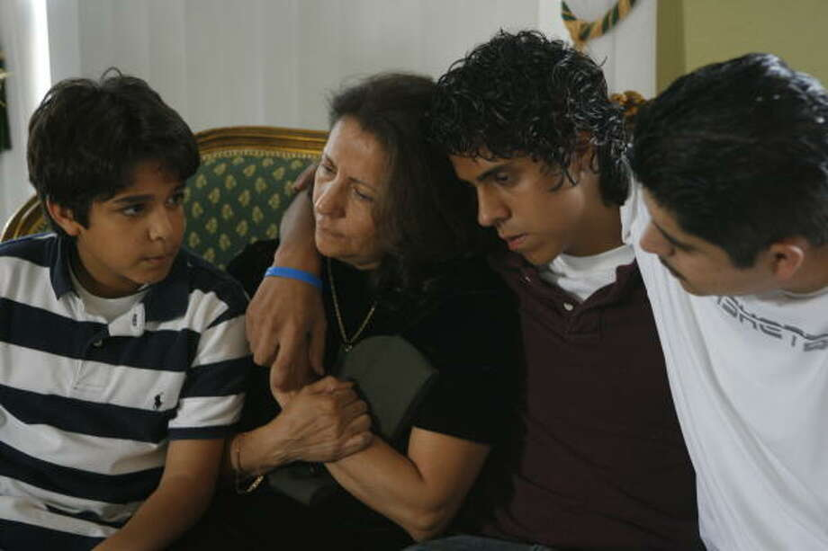 Maria Salgado, the mother of slain Marine Benjamin Rosales, pictured at left, is comforted by her sons, Angel Daher, 11, left; Abraham Daher, 15; and Edgard Rosales Salgado, 25, as she clutches her son's Marine cap. Benjamin Rosales was killed by a roadside bomb in Iraq on Wednesday. Photo: Steve Campbell, Chronicle