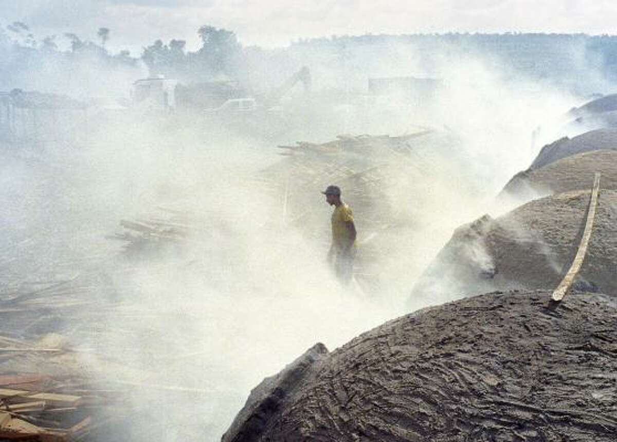 Thick smoke engulfs a man in a charcoal camp in Tucurui, Brazil, in early September. Government inspectors and police discovered 29 slaves working in the camp to supply charcoal used to make pig iron, which is exported to the United States to make steel.