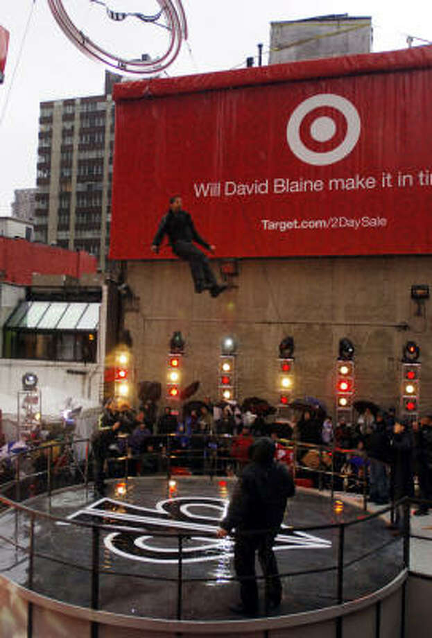 Magician David Blaine jumps to the ground after being shackled in a giant, rotating gyroscope near Times Square in New York for  two days. Photo: JOHN SMOCK, AP