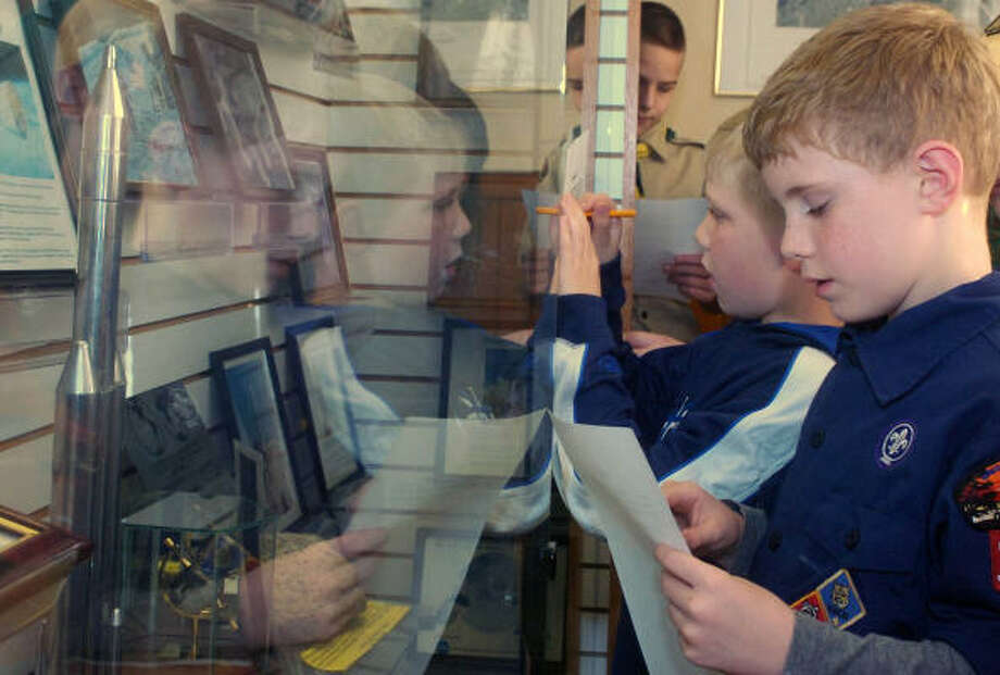 Home-schooler Nathan Wilson, right, looks for an object Tuesday during a scavenger hunt at the Aviation and Military Museum of Louisiana. Photo: MICHAEL DUNLAP, The News-Star