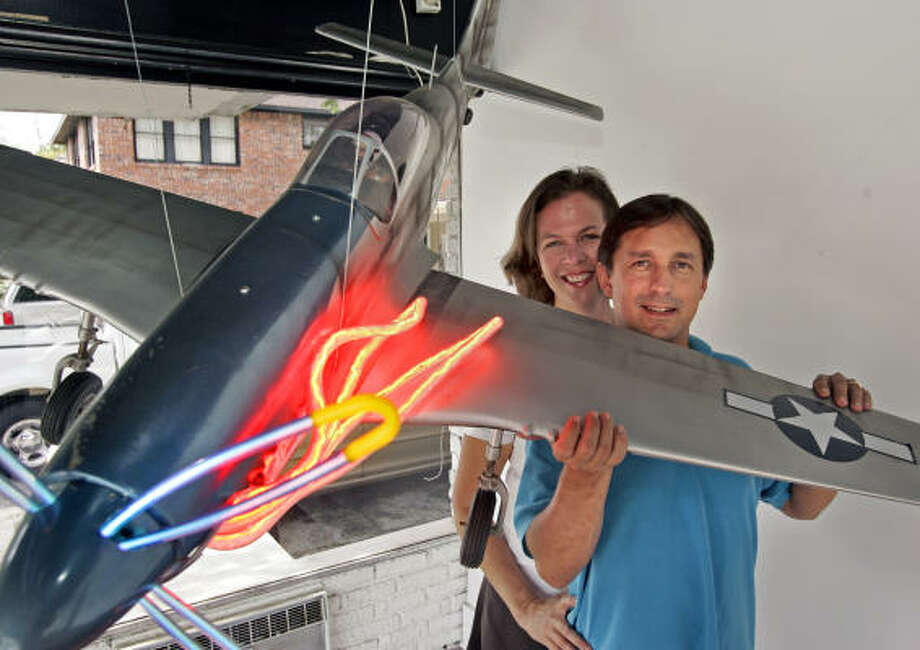 Suzette Walker and Tim Walker, shown with a model of a P-51 Mustang fighter, have kept the Neon Gallery aloft by keeping up with technological advances in the field. Photo: Craig Hartley, For The Chronicle
