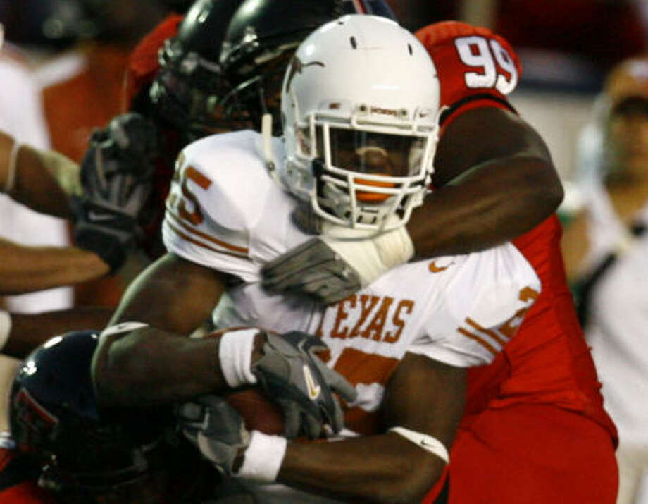 Texas running back Jamaal Charles is wrapped up by Tech defenders in the first quarter. Photo: Nick De La Torre, CHRONICLE