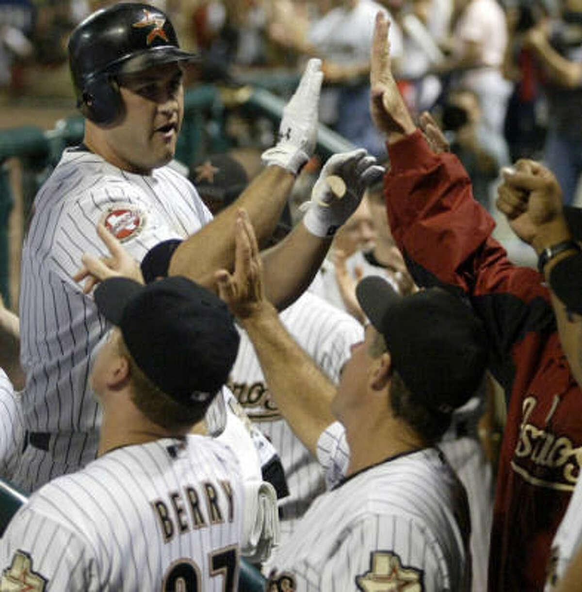 Lance Berkman (top left) is congratulated after a 452-foot home run.