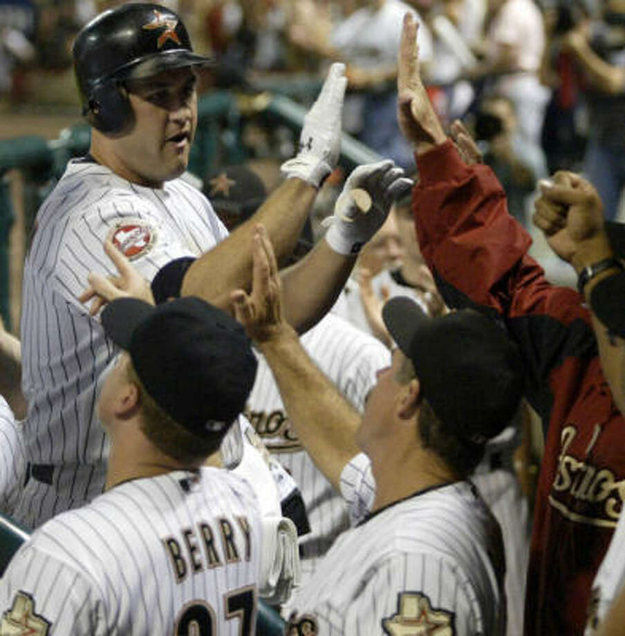 Lance Berkman (top left) is congratulated after a 452-foot home run. Photo: Jessica Kourkounis, For The Chronicle