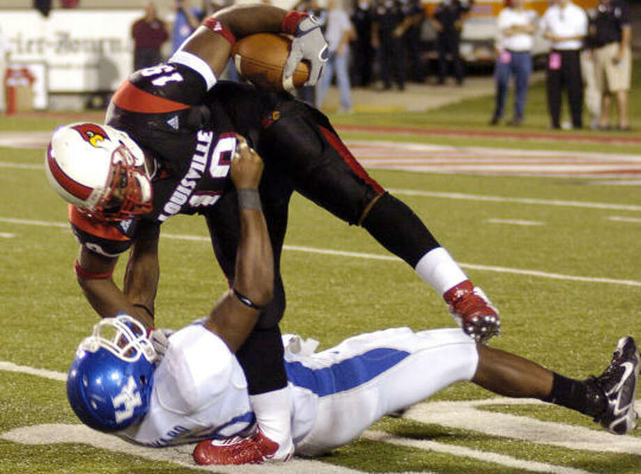 Louisville running back Michael Bush had picked up 128 yards and three touchdowns before breaking his leg on a tackle by Kentucky linebacker Wesley Woodyard. Photo: GAIL KAMENISH, AP