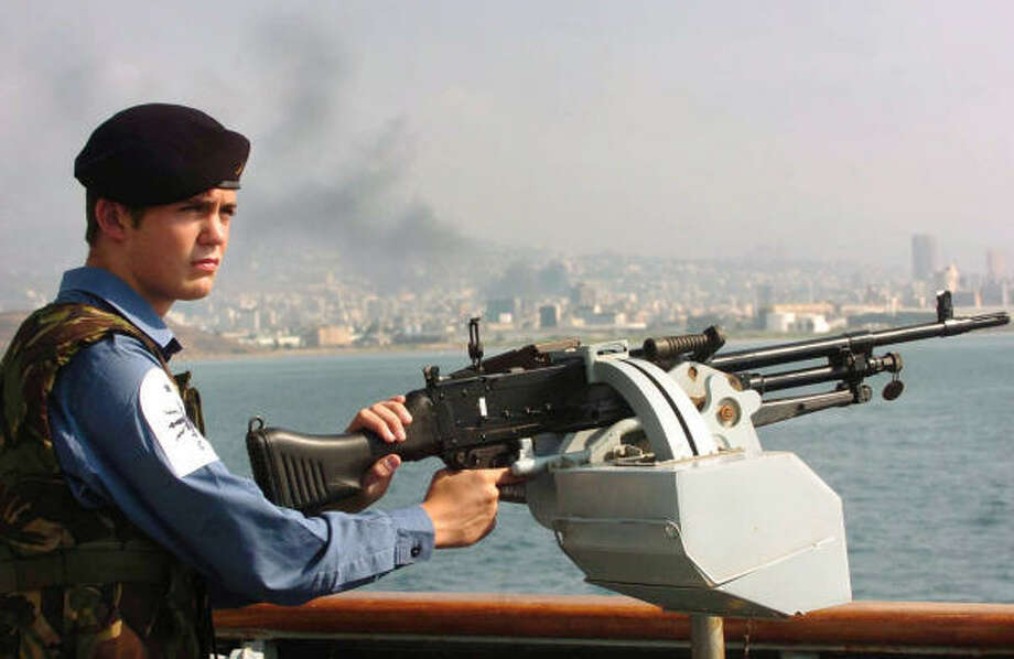 Smoke rises over Beirut today as a British sailor mans a machine gun aboard the Royal Navy ship HMS Gloucester,  which is helping with the evacuation of British nationals from Lebanon. Photo: LUIS HOLDEN, AP