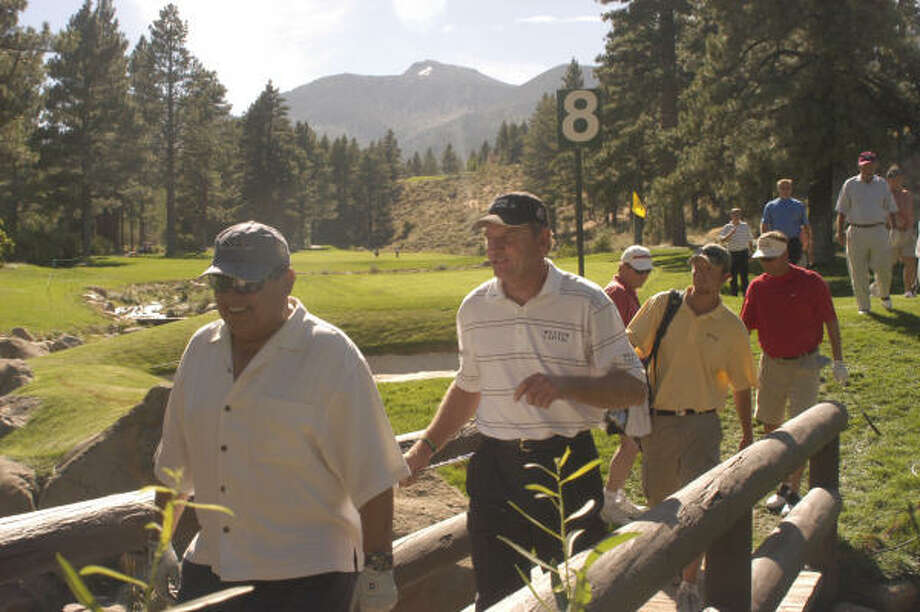 Nick Price, second from left, walks across Galena Creek off the eighth green during the  Reno-Tahoe Open pro-am Wednesday at Montreux Golf and Country Club. Photo: TIM DUNN, AP