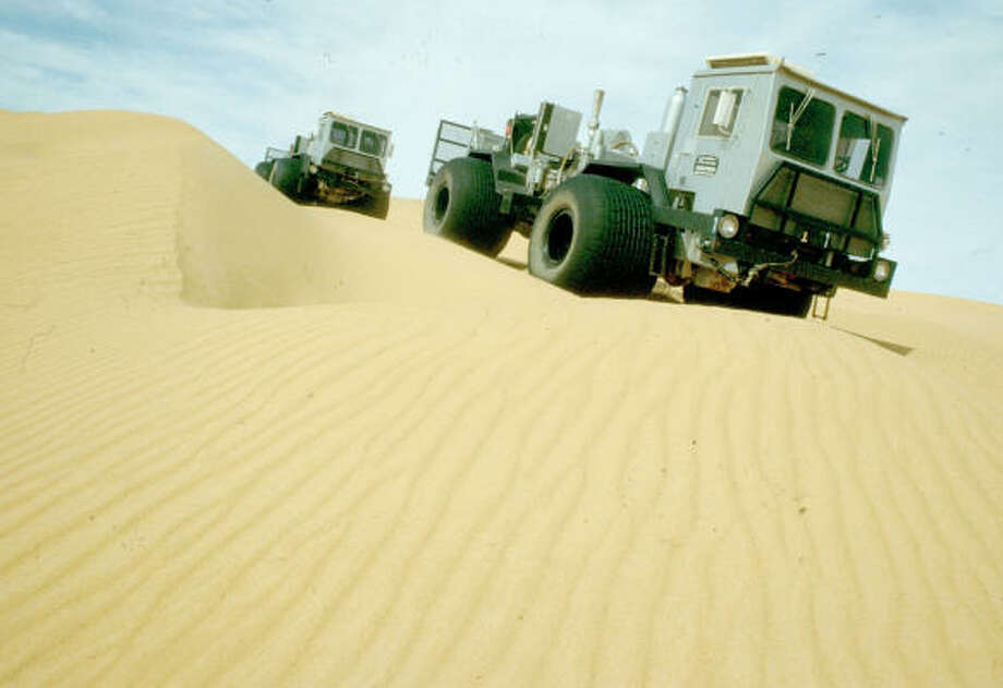 Trucks for seismic surveys operate in sand dunes in the Libyan Sahara. The latest auction of exploration licenses offers high-risk areas that might draw oil companies seeking a start in an underexplored region. Photo: Bloomberg News
