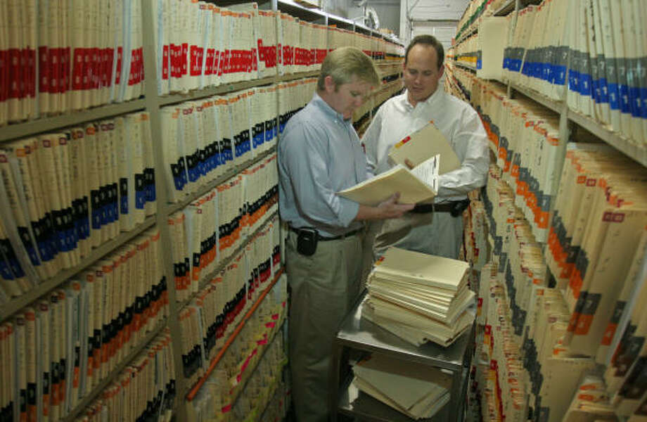 Evan Hughes, left, and Michael Wilde, co-owners of Commerce Restructuring Co., sift through the more than 65,000 documents the company will distribute to former patients of Bellaire Medical Center. Photo: Gary Fountain, For The Chronicle