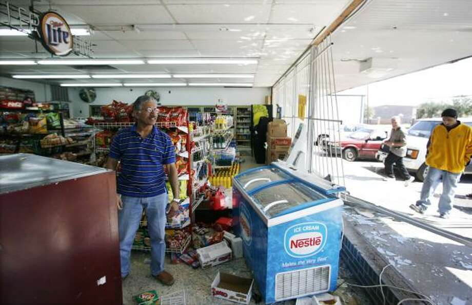 Ijaz Ali surveys the damage done to his southwest Houston store Friday after a suspected burglar drove his pickup through the storefront. Photo: Billy Smith II, CHRONICLE