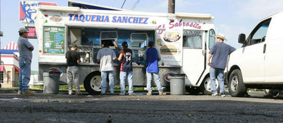 Customers wait for their orders at the Taqueria Sanchez truck on Veterans Memorial Boulevard in Metairie, La. Photo: James Nielsen, Chronicle