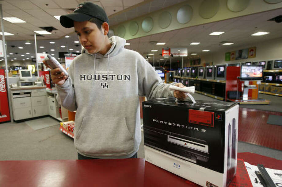 Ruben Sorola checks his text messages after purchasing a PlayStation 3 to see how his buddies fared in their efforts to land machines. Sorola was the second at the Circuit City on San Felipe to buy a console, a 60-gigabyte unit, which he said he intends to sell. Photo: Aaron M. Sprecher, For The Chronicle