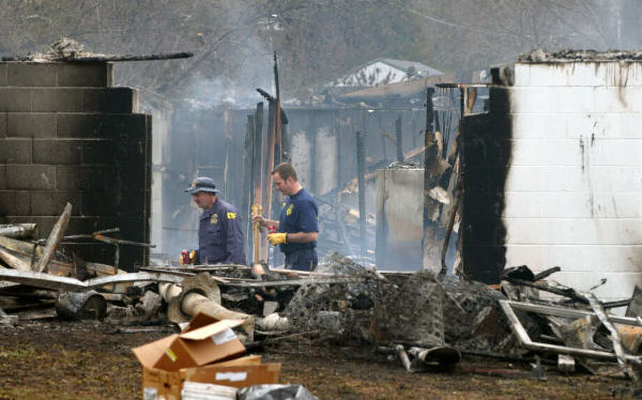 Investigators examine the charred rubble of a group home in Anderson, Mo., where an overnight fire killed 10 people and injured 24. Photo: MIKE GULLETT, AP