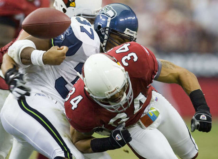 Arizona's Robert Griffith (34) forces Seattle's Shaun Alexander to fumble in the first quarter of Sunday's game at Glendale, Ariz. The Seahawks lost three fumbles, which led to 14 points for the Cardinals. Photo: David Wallace, AP